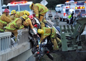 Jan. 12, 2012 - Buellton, California, U.S. - Firefighters rescue a San Juan Capistrano family from a car dangling over a bridge after a fiery crash on Highway 101 near Buellton. Fire crews use a US Navy SEEBEE heavy forklift to stabilize the BMW that was dangling over the side of the bridge. A mother and her two daughters were taken to the hospital. (Credit Image: © Mike Eliason/Santa Barbara News-Press/ZUMAPRESS.com)